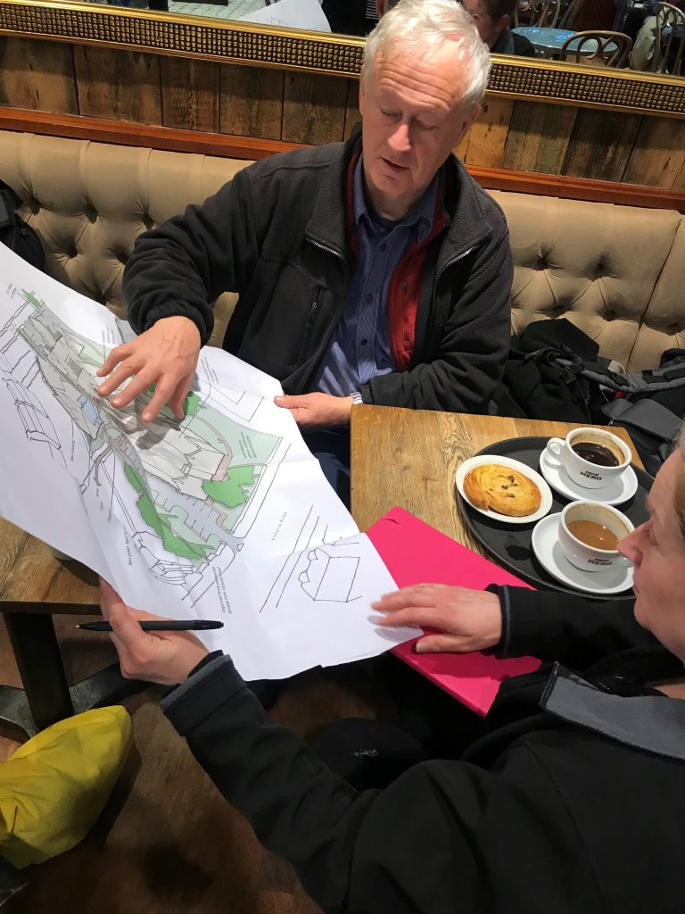 A man and a woman are sitting at a table with two coffees, they are both looking at a large paper showing a drawing of a building