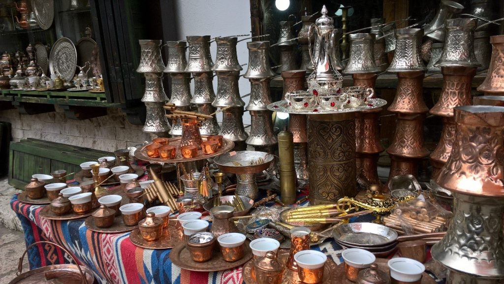 Many brass or copper tea cups and jugs on a table at a market.